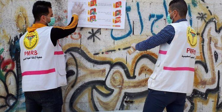 Medewerkers van de Palestinian Medical Relief Society verspreiden posters in Gaza om mensen bewust te maken van het besmettingsgevaar van het coronavirus.